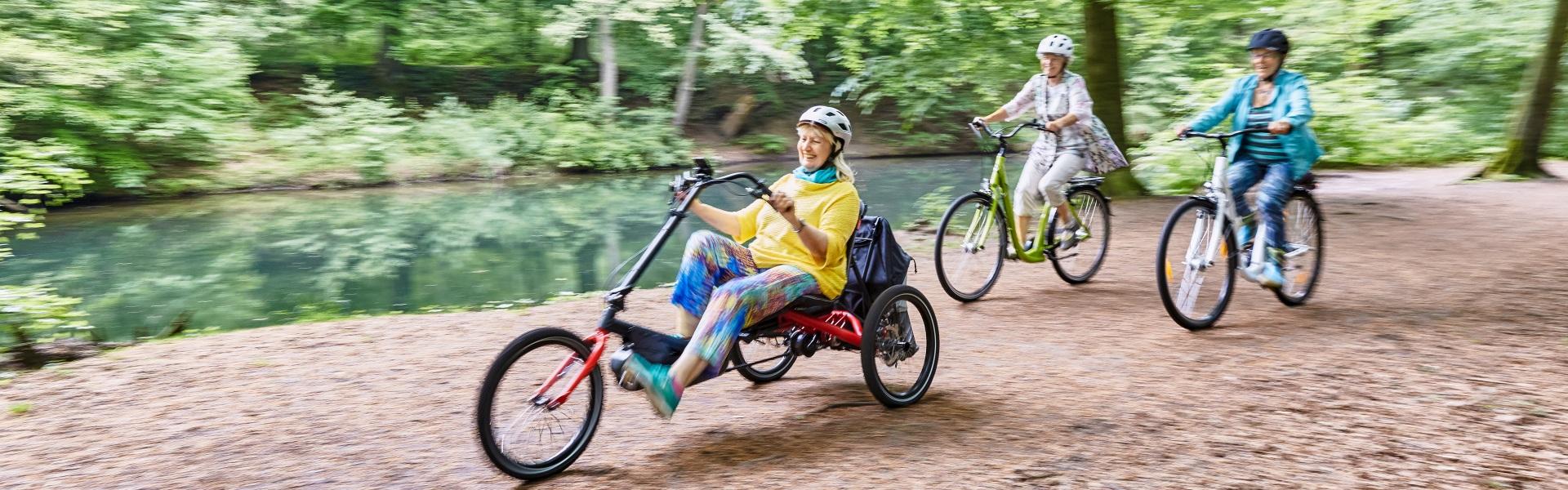 Frau fährt auf ihrem HASE BIKES Delta-Trike mit zwei Freundinnen durch den Wald