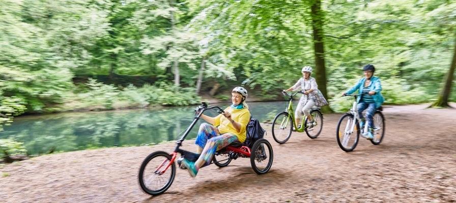 Frau auf HASE BIKE Liegedreirad fährt durch den Wald