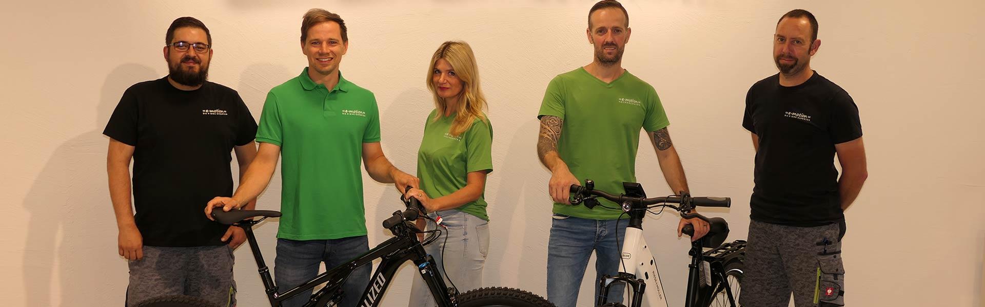 Drei Mitarbeiter vor Shopwand der e-motion e-Bike Welt Pforzheim_01_21