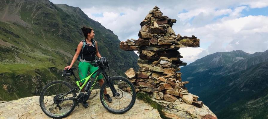 Die Geschäftsführerin der e-motion e-Bike Welt Fuchstal steht mit e-Bike auf einem Berg
