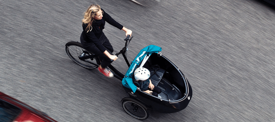 Frau fährt mit ihrem Kind im Triobike Lastenrad durch die Stadt