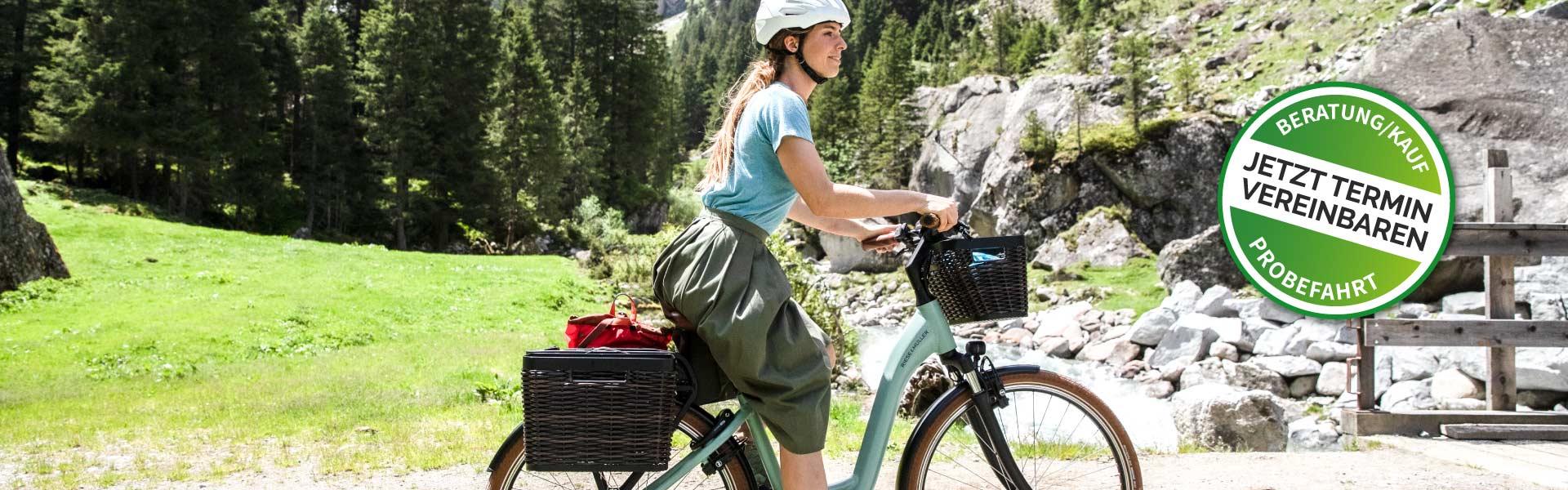 Frau fährt auf einem e-Bike in einer Bergandlandschaft