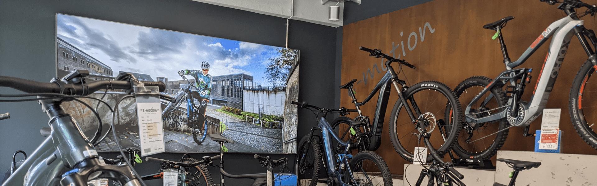 verschiedene e-Mountainbikes mit Nahaufnahme vom Vorderrad vor Leinwand 1920x600