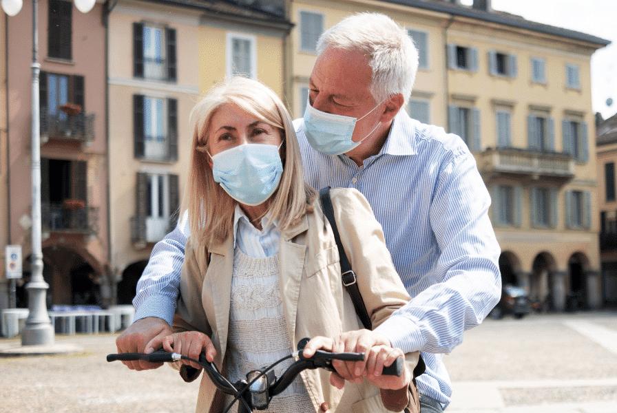 Ein älteres Paar mit Masken auf einem e-Bike