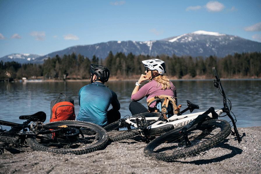 Zwei Specialized Fahrer sitzen zur Pause an einem See