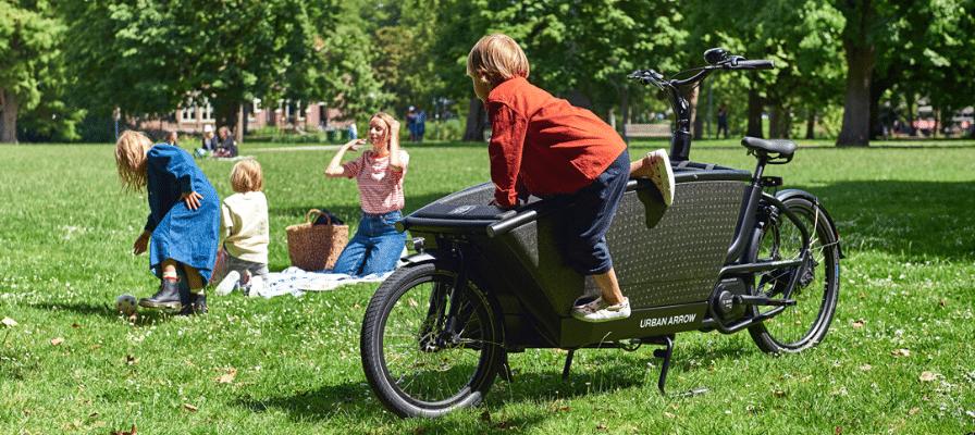 Kinder spielen auf einer Wiese neben dem Urban Arrow Family Lastenrad