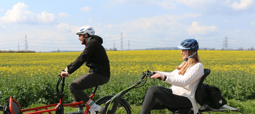 Ein Mann und eine Frau fahren mit ABUS Helmen auf ihrem Lastenrad und Dreirad