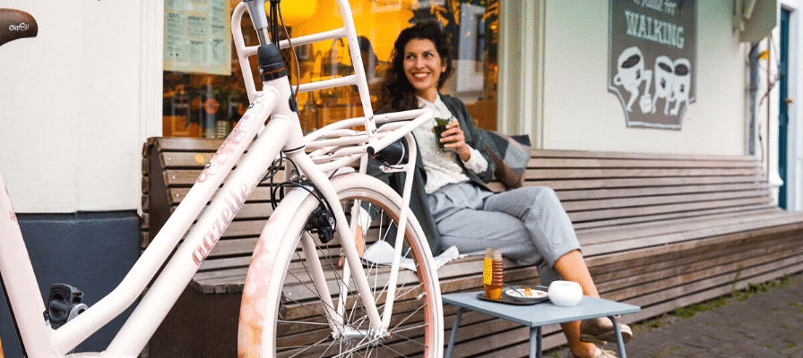Frau sitzt neben dem Gazelle Miss Grace e-Bike