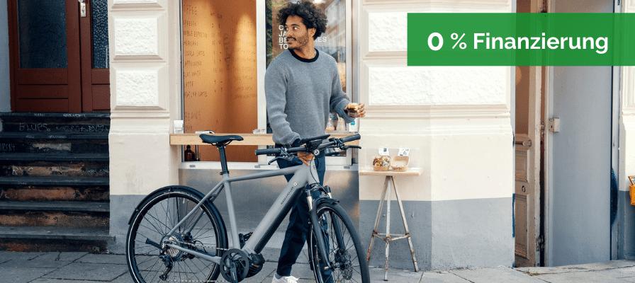 Ein Mann schiebt sein Riese & Müller e-Bike und hält dabei einen Kaffee