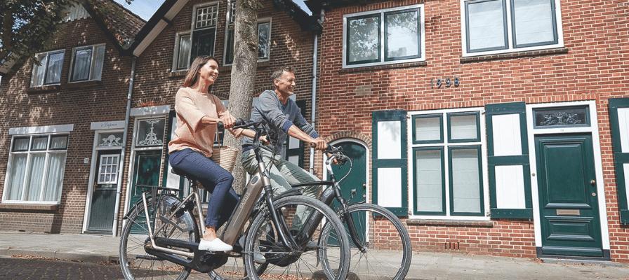 Eine Frau und ein Mann fahren lachend auf zwei e-Bikes