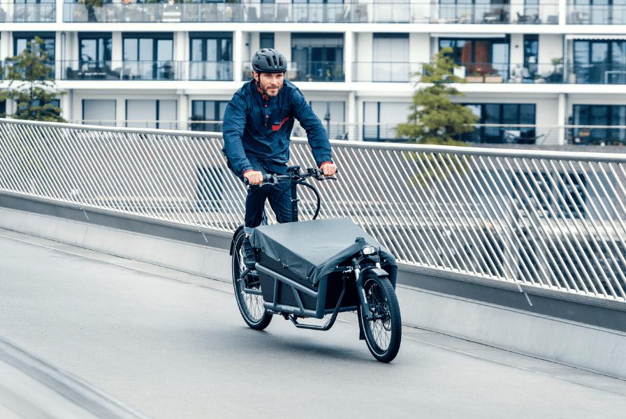 Mann fährt auf seinem Riese & Müller Lastenrad über eine Brücke