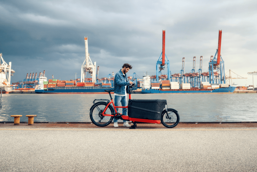 Mann steht neben seinem Riese & Müller Lastenrad vor einem Hafenbecken
