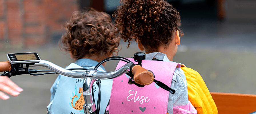Zwei Kinder von hinten im Lastenrad
