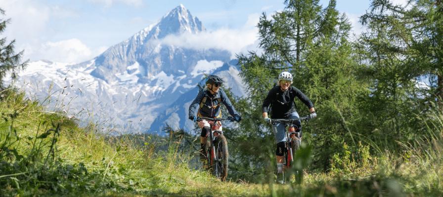 Zwei Fahrer auf ihren e-Mountainbikes vor einer Bergkulisse