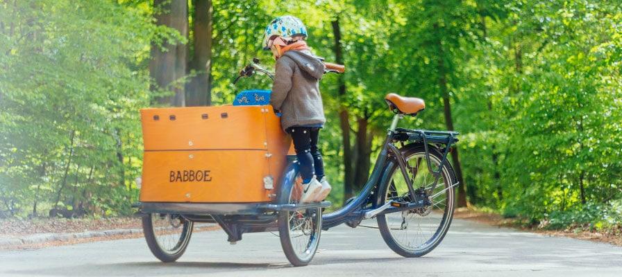 Kind steht auf dem Babboe Lastenrad und schaut in die Box