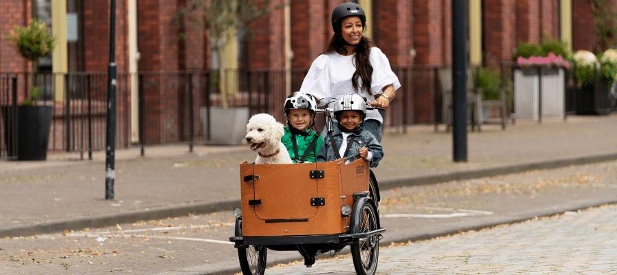 Frau mit Kindern und Hund auf einem Lastenrad von Babboe