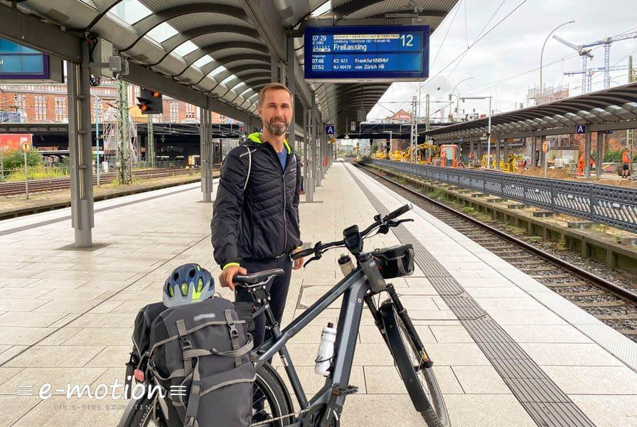 Mann mit Fahrrad am Bahnhof