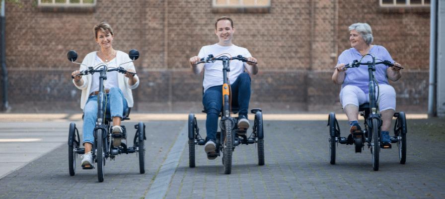 Mann und Frauen auf Dreirädern