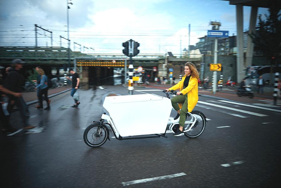 Eine Frau fährt auf einem Cargobike durch die Straße