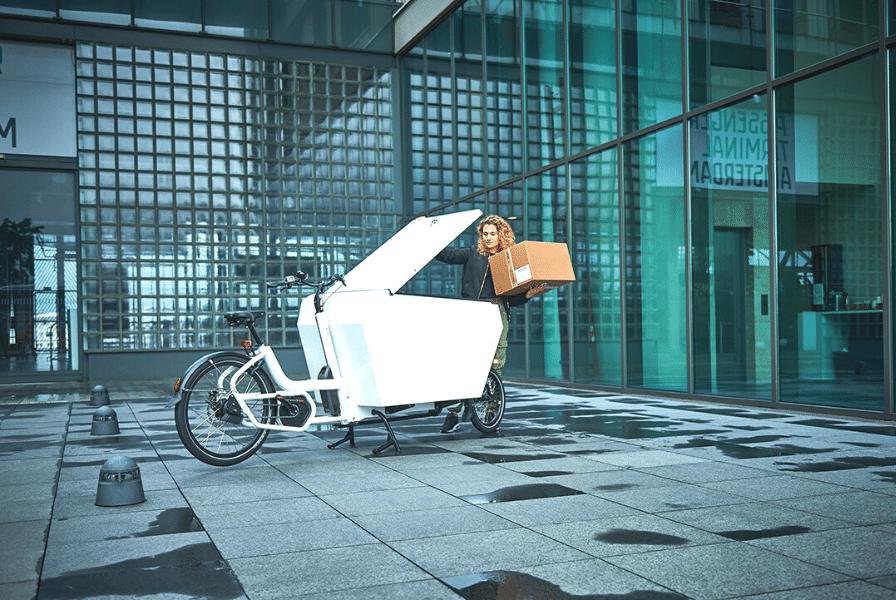 Eine Frau transportiert Pakete mithilfe eines Lastenfahrrads