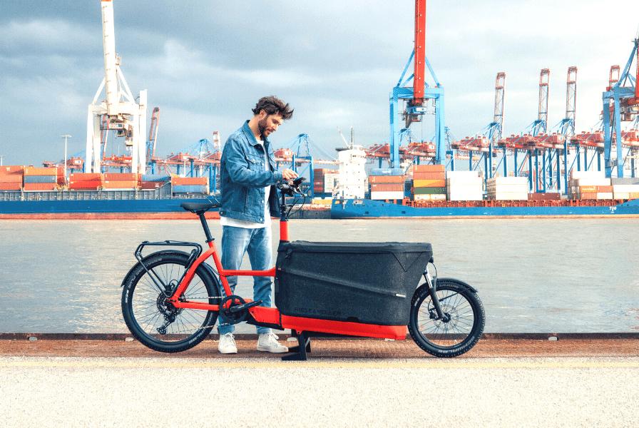 Ein Mann steht an seinem Lastenrad an einem Hafen