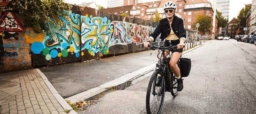 Fahrerin mit Sonnenbrille fährt mit ihrem Liv e-Bike vor einer Graffiti Wand