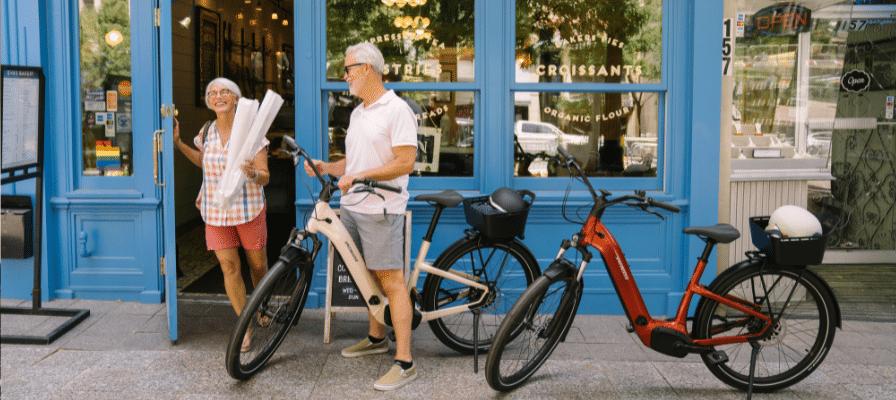 Ein älteres Ehepaar kauft mit dem e-Bike ein