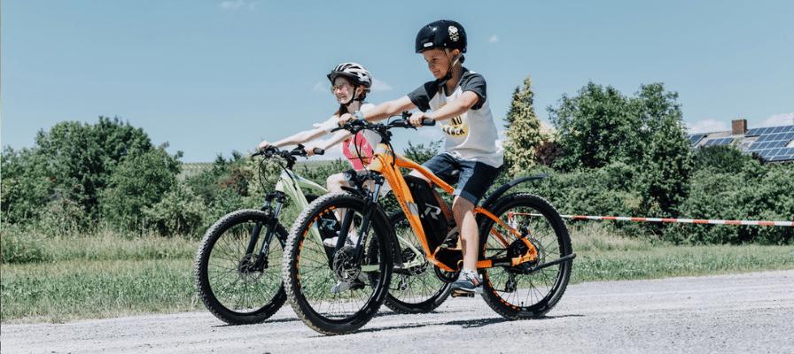 Ein Junge und ein Mädchen fahren auf einem e-Bike über eine Straße