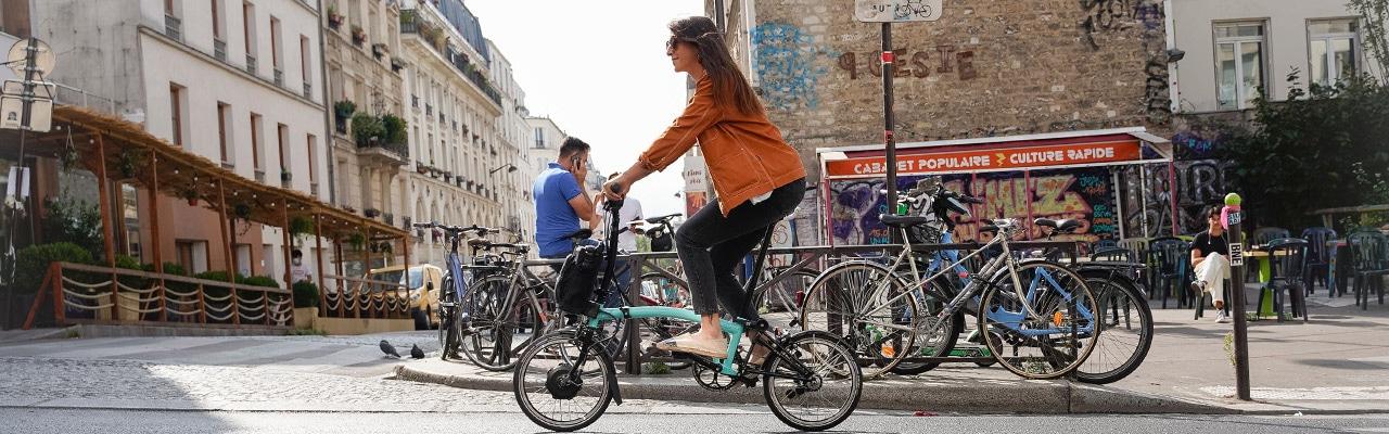 Eine Frau fährt mit einem praktischen Bromtpon Falt/Kompakt e-Bike durch die Stadt