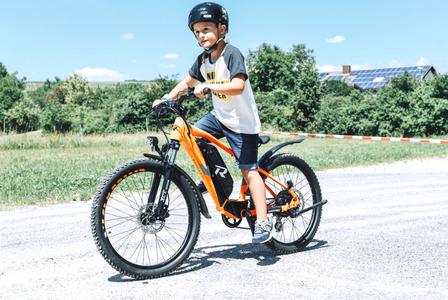 Ein Junge fährt ein e-Bike auf der Straße
