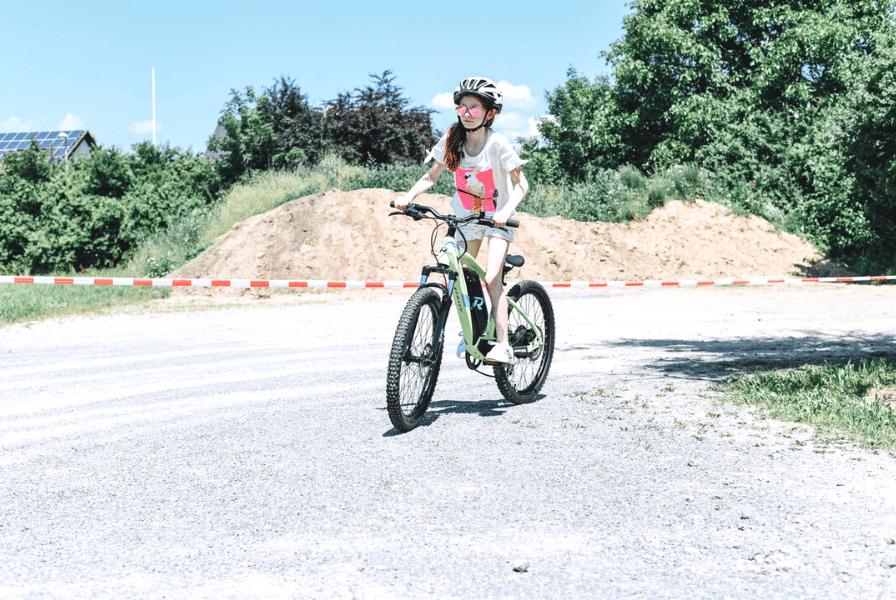 Ein Mädchen fährt auf einem e-Bike auf der Straße