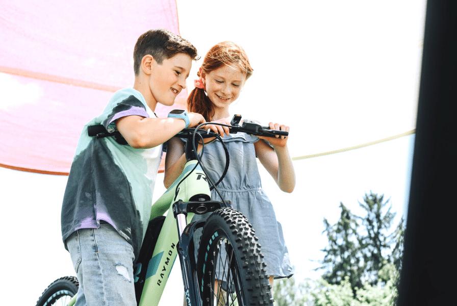 Ein Junge und ein Mädchen betrachten ein e-Bike aus der Nähe