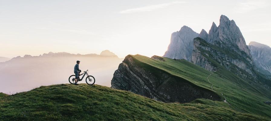 Mann steht mit dem Erzberg M1 an dem Hang eines Berges