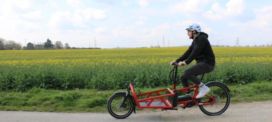 Testfahrer fährt mit rotem Riese & Müller Load an einem Feld vorbei