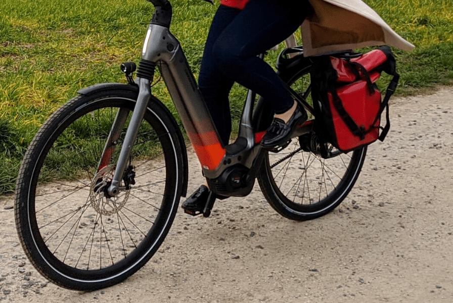 Eine Frau fährt mit dem e-Bike über Schotter