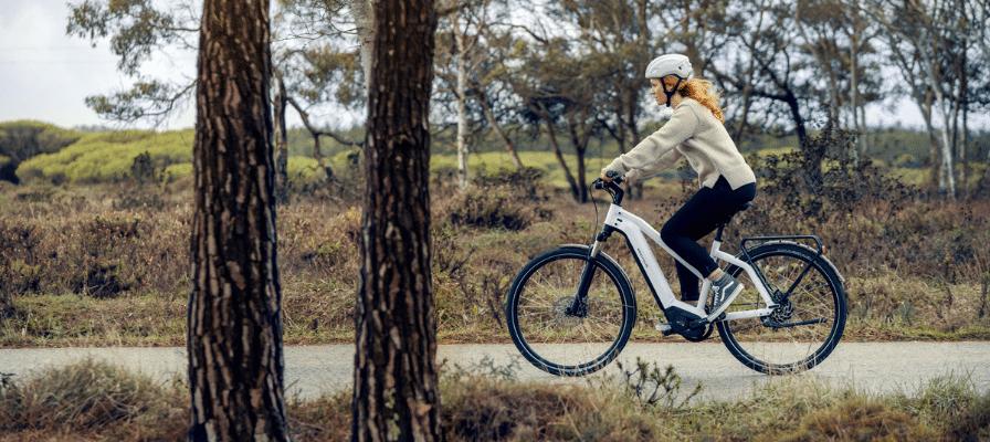 Eine Frau fährt mit dem Charger3 Mixte von Riese und Müller durch die Straße