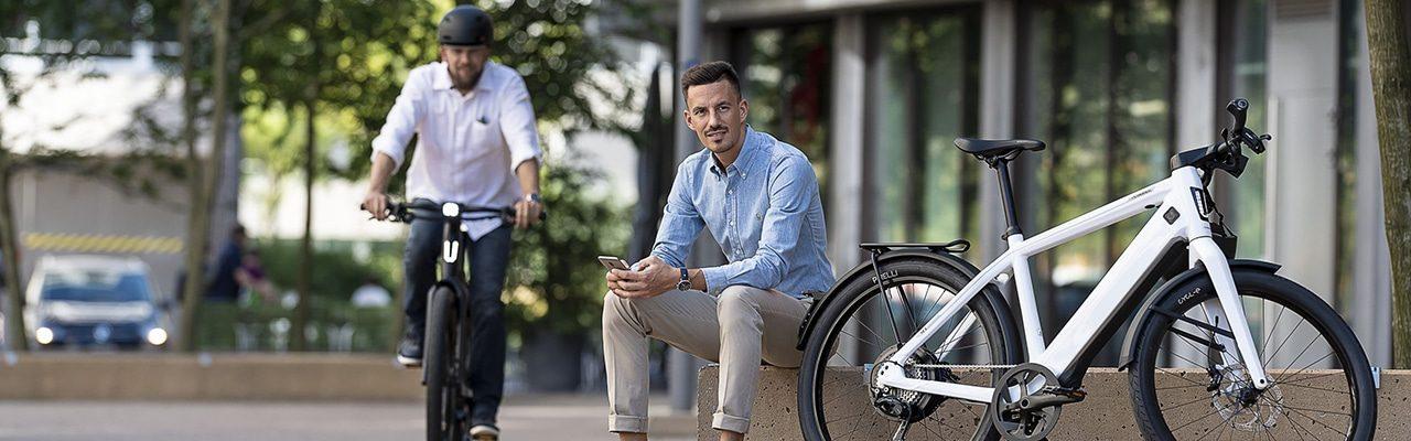 e-Bike Fahrer mit Handy sitzt neben weißem Stromer e-Bike