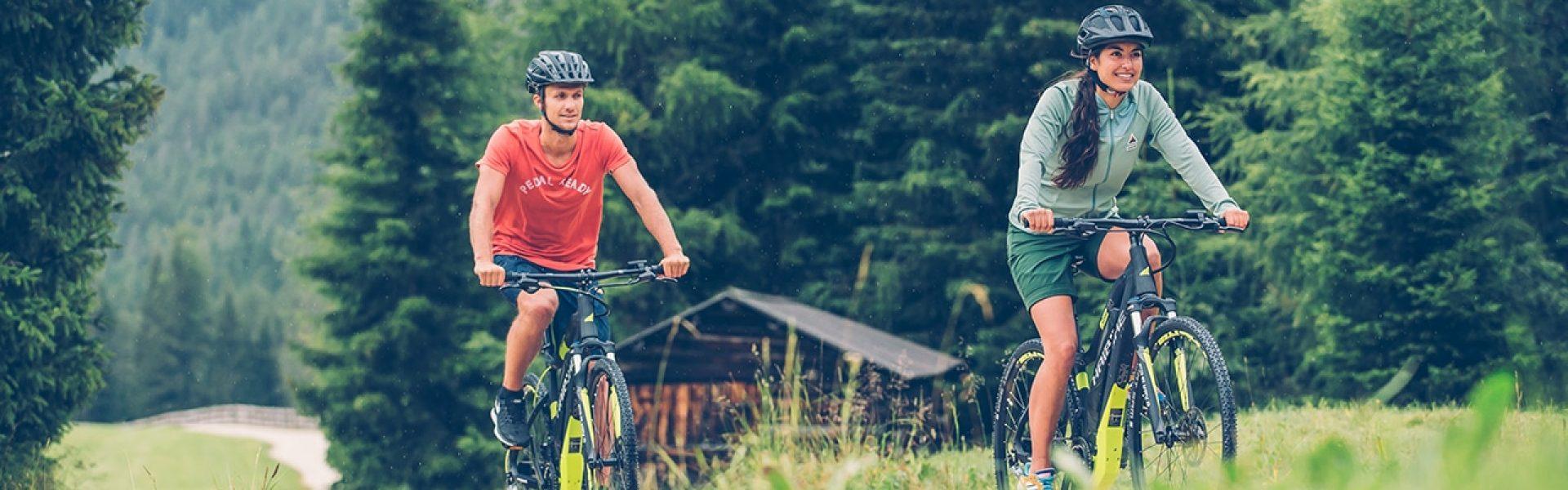 Sportliches Paar fährt mit ihren Cross e-Bikes von Haibike über einen Schotterweg in den Bergen